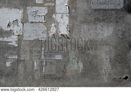 Surface Of An Old Weathered Bulletin Board With Remnants Of Torn Paper Ads, Abstract Grunge Backgrou