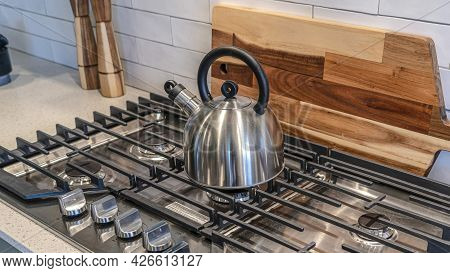 Pano Kettle On Top Of A Cooktop Against Wooden Chopping Board And Tile Backsplash