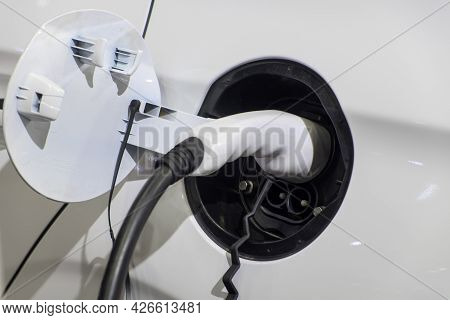 Close-up Gripping Of Electric Charge Machine Connected With Plug For Charging Battery On White Smart