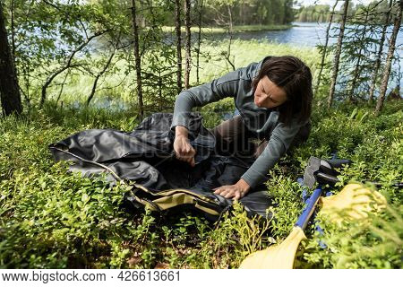 Woman Unfolds A New Rubber Boat, Oars Are Lying Nearby, Against The Backdrop Of A Lake. Preparing Fo