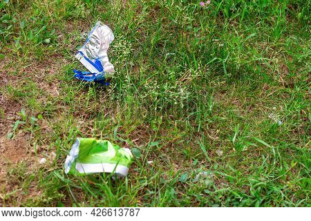 Selective And Soft Focus Of Wrappers Lying On The Green Grass. The Concept Of Environmental Pollutio