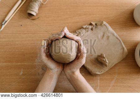 Potter Works With Clay, Close-up Top View Female Hands Hold A Piece Of Wet Clay In Their Hands. The