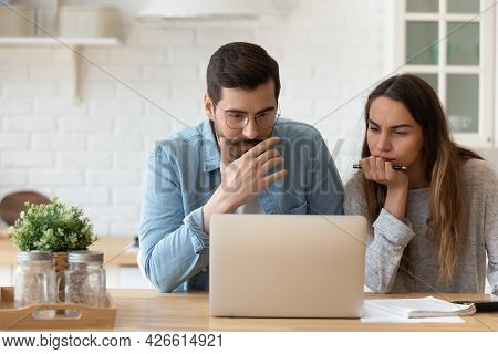 Serious Concerned Couple Sit Indoor Looking At Laptop Read News