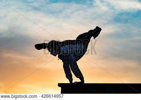 Silhouette Of Flexible Female Circus Artist Doing Handstand On The Dramatic Sunset. Concept Of Indiv
