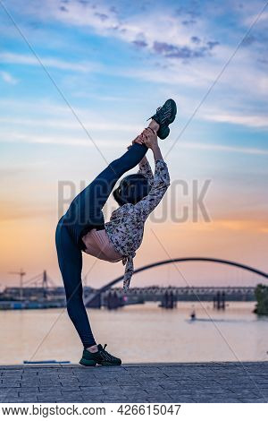 Silhouette Of Flexible Female Woman Keeps Balance Gymnastic On Split On The Dramatic Sunset. Concept