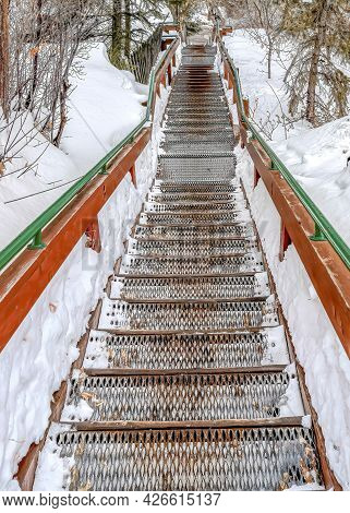 Vertical Outdoor Stairway With Grated Metal Treads In A Snowy Mountain Town In Winter