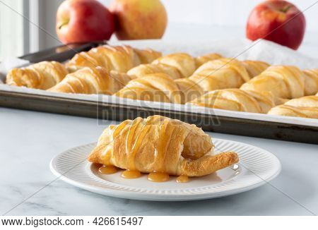 Close Up Of An Apple Filled Crescent Roll Topped With Caramel Sauce And A Baking Sheet Of More Rolls