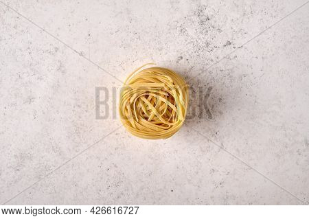 Uncooked Raw Fettuccine On Grey Textured Background. Copy Space. Top View
