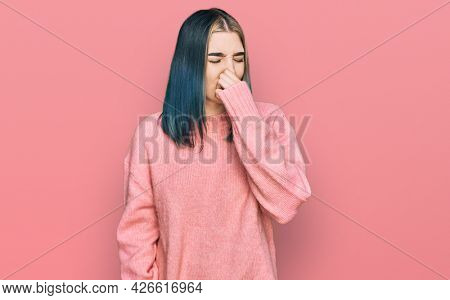 Young modern girl wearing pink wool winter sweater smelling something stinky and disgusting, intolerable smell, holding breath with fingers on nose. bad smell