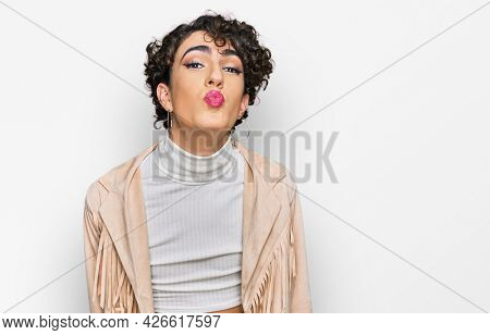Handsome man wearing make up and woman clothes looking at the camera blowing a kiss on air being lovely and sexy. love expression.