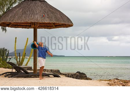 Happy Caucasian Boy Plays On One Of The Best Mauritius Beach On Rainy Cloudy Day, Catches Ball To Fl