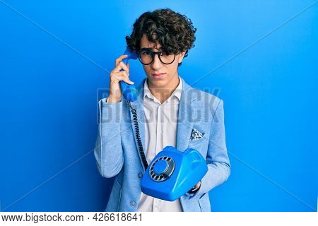 Hispanic young man speaking on vintage telephone skeptic and nervous, frowning upset because of problem. negative person.