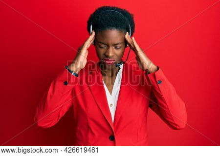 Young african american girl wearing call center agent headset suffering from headache desperate and stressed because pain and migraine. hands on head.