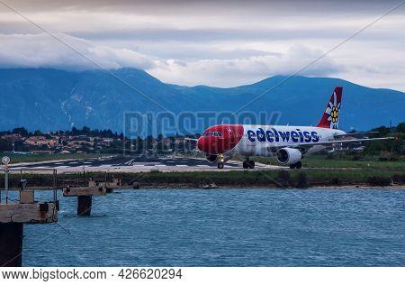 Corfu Island, Greece- May 4, 2019: View Of Edelweiss Airplane On Runway Of Corfu Airport, Sea, Villa