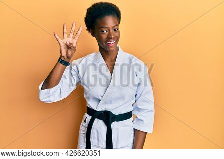 Young african american girl wearing karate kimono and black belt showing and pointing up with fingers number four while smiling confident and happy.