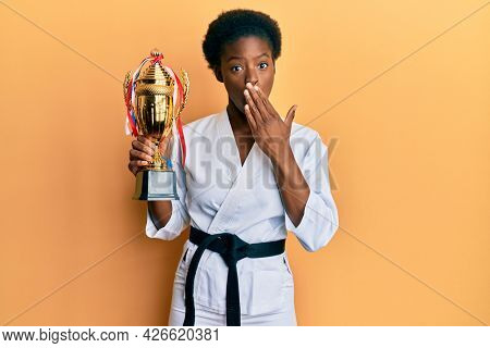 Young african american girl wearing karate kimono holding trophy covering mouth with hand, shocked and afraid for mistake. surprised expression