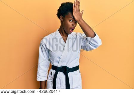 Young african american girl wearing karate kimono and black belt surprised with hand on head for mistake, remember error. forgot, bad memory concept.
