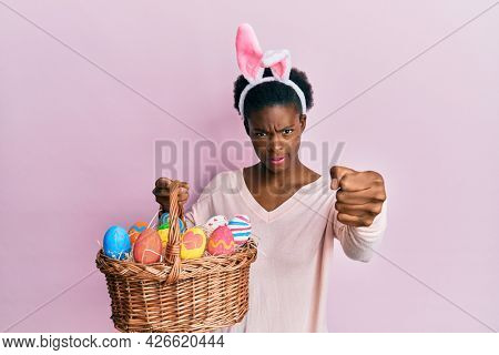 Young african american girl wearing cute easter bunny ears holding basket with painted eggs annoyed and frustrated shouting with anger, yelling crazy with anger and hand raised