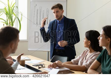 Serious Presenter Giving Marketing Training To Diverse Team Of Employees