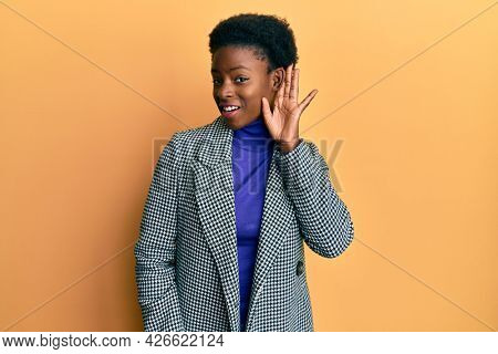 Young african american girl wearing casual clothes smiling with hand over ear listening and hearing to rumor or gossip. deafness concept.