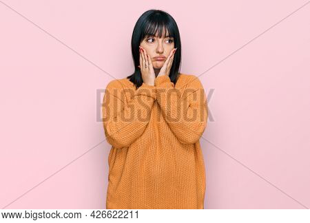 Young hispanic woman wearing casual clothes tired hands covering face, depression and sadness, upset and irritated for problem