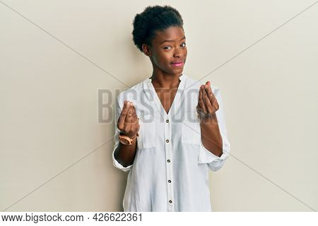 Young african american girl wearing casual clothes doing money gesture with hands, asking for salary payment, millionaire business