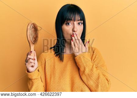 Young hispanic woman holding comb loosing hair covering mouth with hand, shocked and afraid for mistake. surprised expression
