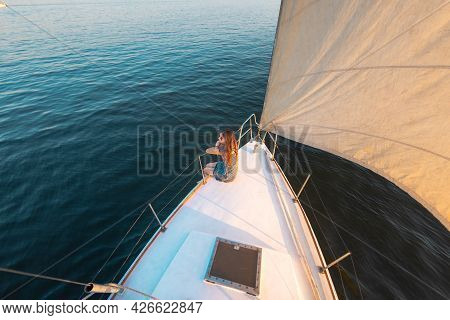Travel On A Yacht. A Young Girl Sits On The Stern Of A White Yacht. Privacy While Traveling.
