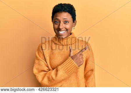 Young african american girl wearing casual clothes cheerful with a smile of face pointing with hand and finger up to the side with happy and natural expression on face