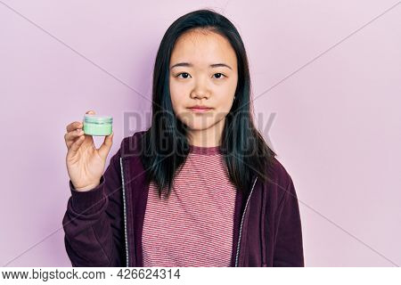 Young chinese girl holding cosmetic moisturizer facial cream thinking attitude and sober expression looking self confident