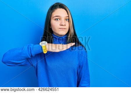 Young brunette girl wearing turtleneck sweater cutting throat with hand as knife, threaten aggression with furious violence