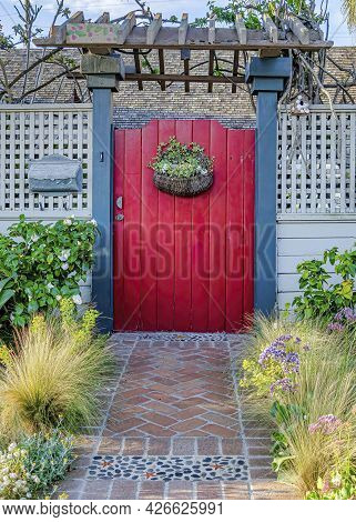 Vertical Landscaped Garden With Pathway Inside White Fence And Red Gate With Pergola