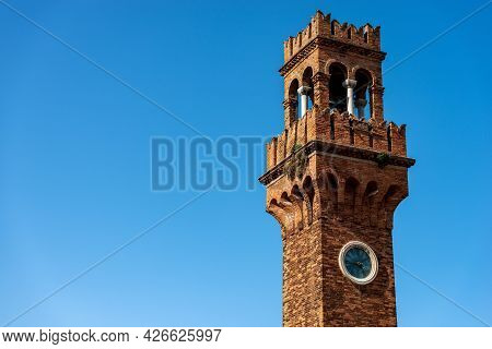 Close-up Of The Ancient Civic Tower Or Clock Tower In Murano Island In Medieval Style. Campo Santo S