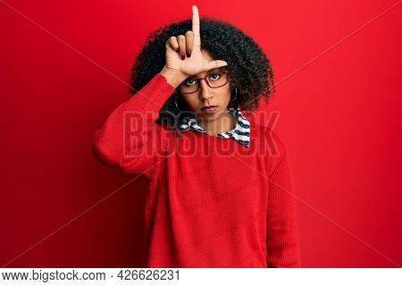 Beautiful african american woman with afro hair wearing sweater and glasses making fun of people with fingers on forehead doing loser gesture mocking and insulting.