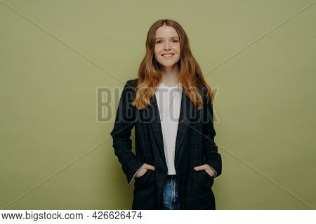 Happy Fashionable Cheerful Teenage Girl Wearing Blazer And Jeans With Keeping Hands In Pockets And S