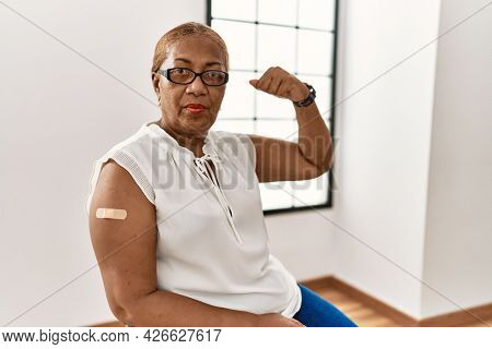 Mature hispanic woman getting vaccine showing arm with band aid strong person showing arm muscle, confident and proud of power