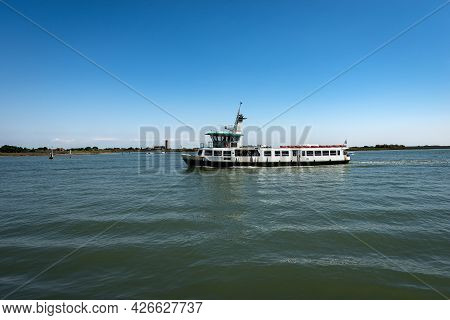 Ferry Boat In Motion In The Venice Lagoon In Front Of Torcello And Burano Island. On The Horizon The