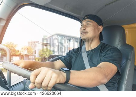 Happy Smiling Truck Driver Bearded Male Fastens His Seat Belt While Driving. Delivery Man Transport