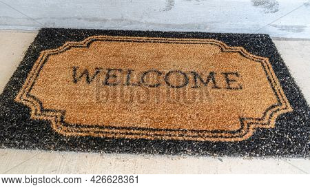 Pano Home Entrance With Welcome Doormat In Front Of The Doorstep And Gray Front Door