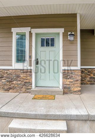 Vertical Front Door And Sidelight Against Brick Wall And Wood Siding Of Home With Porch