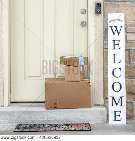 Square Boxes Stacked In Front Of White Wooden Front Door Of Home With Welcome Sign