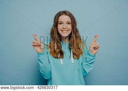 Excited Smiling Young Girl With Wavy Ombre Hair Keeping Fingers Crossed Looking At Camera Wearing Ca