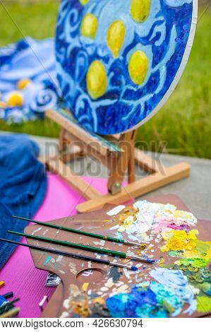 Palette With Multi-colored Paints And Brushes, Woman Painting Picture. High Quality Photo