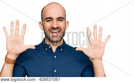 Young hispanic man wearing casual clothes showing and pointing up with fingers number ten while smiling confident and happy.