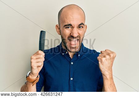 Young hispanic man holding comb loosing hair screaming proud, celebrating victory and success very excited with raised arms
