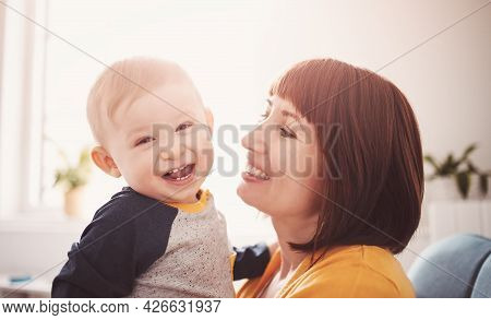 Happy Mother Holding In Her Arms Her Smiling Son.