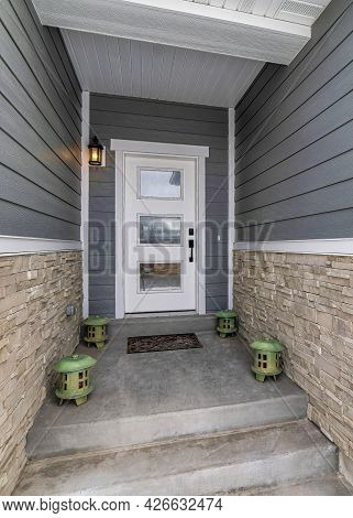 Vertical Concrete Steps And Lanterns At The Home Entrance With Glass Paned Front Door