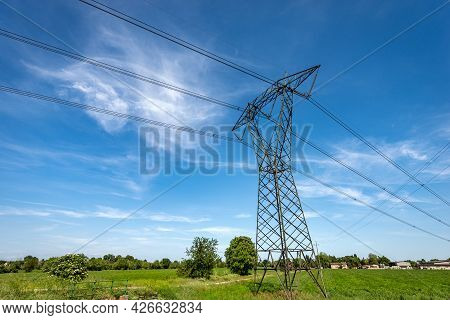 High Voltage Tower, Power Line With Electric Cables And Insulators In Countryside Against A Blue Sky