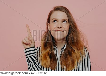 Pretty Young Woman In Formal Striped Black And White Blouse Biting Lower Lip, Demonstrating Thinking
