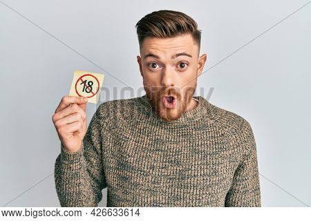 Young redhead man holding under 18 prohibition sticker scared and amazed with open mouth for surprise, disbelief face